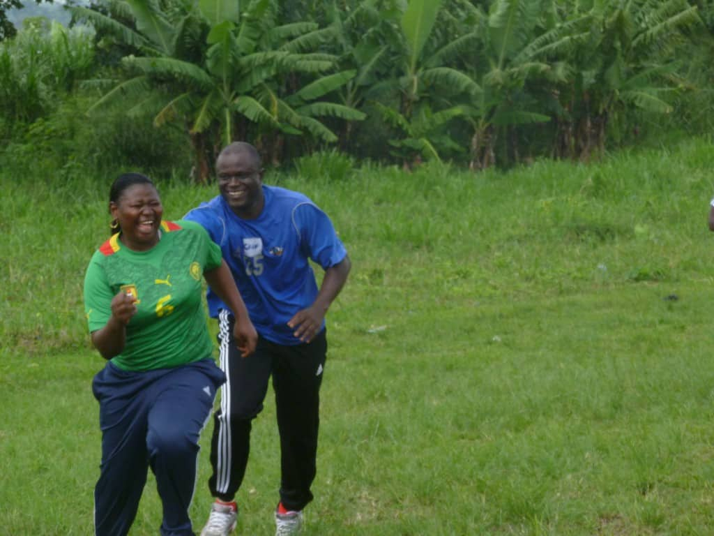 Coaches Across Continents' participant Martha runs away from Community Impact Coach Kama.