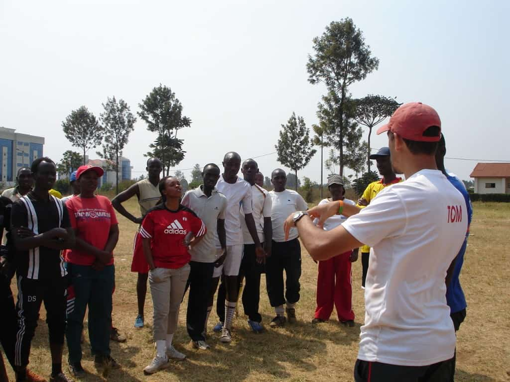 Coach Tom speaks to his new Rwandan friends
